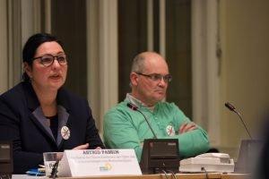 Auf dem Bild ist Astrid Passin zu sehen, die Sprecherin der Hinterbliebenen der Opfer des Terroranschlags. Sie sitzt auf dem Podium und redet. Im Hintergrund sitzt Andreas Schwartz.