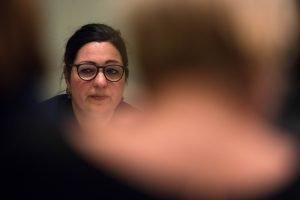 Auf dem Bild ist Astrid Passin zu sehen, die Sprecherin der Hinterbliebenen der Opfer des Terroranschlags. Sie sitzt auf dem Podium und redet.