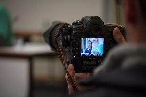 Auf dem Bild ist eine Kamera zu sehen, auf deren Bildschirm Andreas Schwartz zu sehen ist, der auf dem Podium redet.