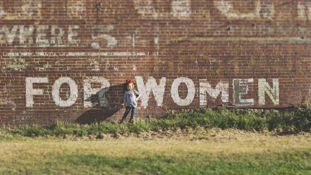 """Es ist ein junges Mädchen zu sehen, das vor einer Wand steht, auf der """"For Woman"""" steht"""