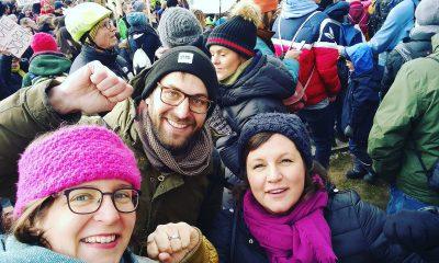 Drei Abgeordnete recken die Fäuste in die Luft und lächeln. Im Hintergrund ist eine Demonstration von Schülerinnen und Schüler, Studentinnen und Studenten, die für Klimaschutz kämpfen.
