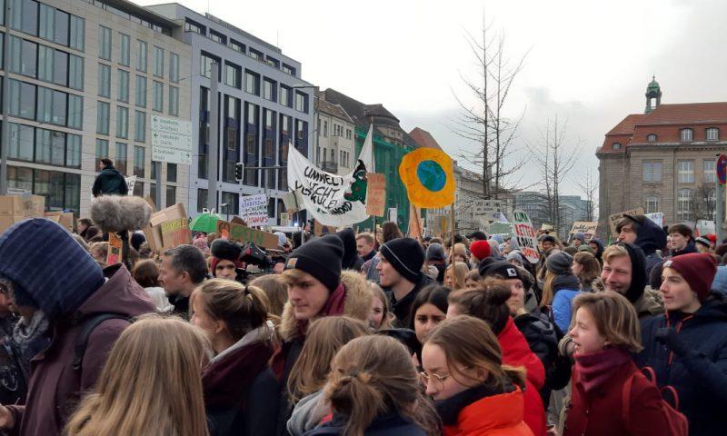 Schülerinnen und Schüler, Studentinnen und Studenten demonstrieren auf der Straße, zeigen Bilder in die Höhe.