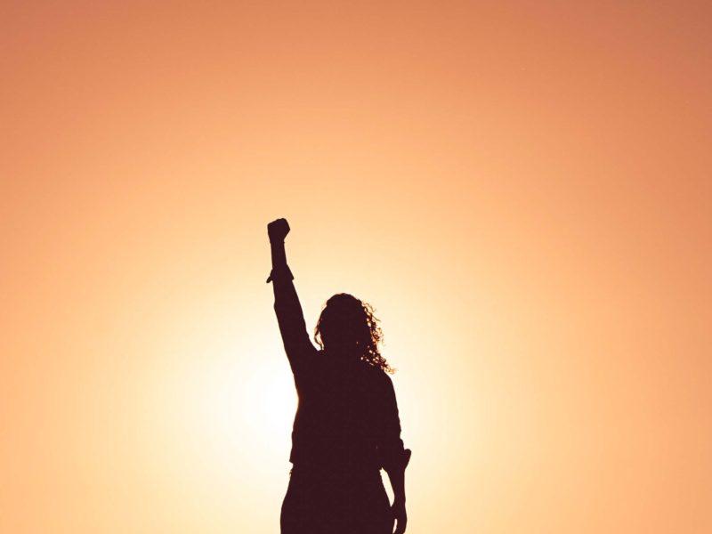 Eine Frau steht im Sonnenuntergang und streckt die geballte Faust in die Luft