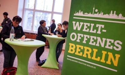 """Es ist ein grünes Banner mit der Aufschrift """"Weltoffenes Berlin"""" im Vordergund zu sehen"""