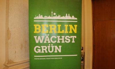 """Es ist eine grüne Stellwand zu sehen, auf der """"Berlin wächst grün"""" steht"""