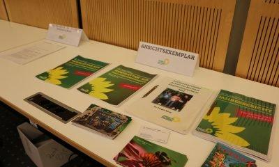Es ist Informationsmaterial von Turgut Altug zu sehen, welches auf einem Tisch ausliegt