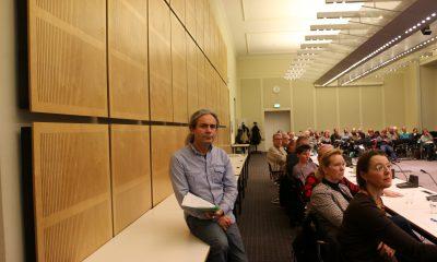 Es ist Turgut Altug zu sehen, der während einer Veranstaltung auf einem Tisch sitzt