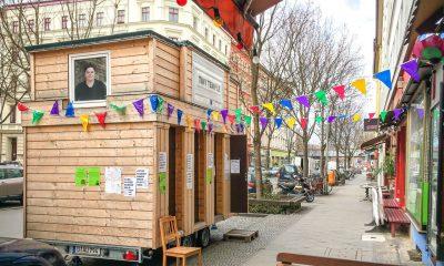 Ein Tiny House steht auf einem Gehweg vor einem grünen Bürgerbüro. Daran sind bunten Fahnen aufgehangen. Im Fenster sieht man das Bild von unserer Abgeordneten Marianne Burkert-Eulitz.