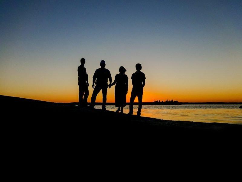 Es ist die Silhouette einer Familie im Sonnenuntergang zu sehen