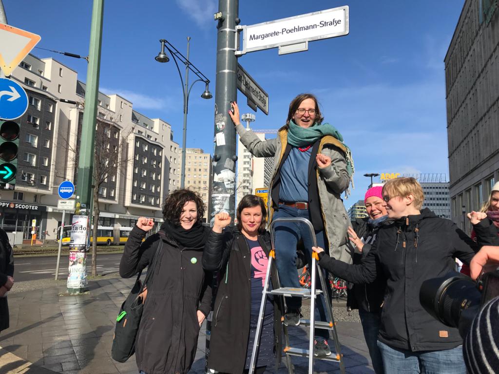 Es sind Silke Gebel, Anja Kofbinger und Antje Kapek am Frauentag in Berlin zu sehen, wie sie ein Straßenschild umbenennen
