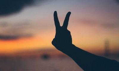 Es ist eine ausgestreckte Hand, die das Friedens-zeichen hochhält, vor dem Sonnenuntergang zu sehen