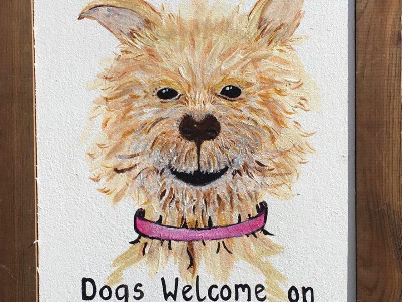Es ist ein Schild zu sehen, auf dem ein Hundekop gemalt ist