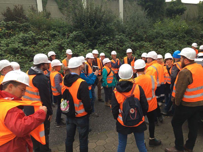 Es sind die Mitglieder der Grünen Fraktion Berlin in orangenen Schutzwesten und weißen Helmen zu sehen