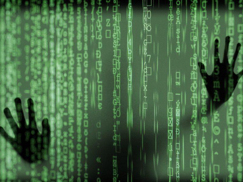 Es ist eine Silhouette hinter einer virtuellen Wand aus Daten zu sehen
