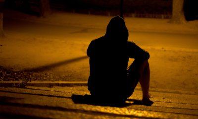 ein Mensch sitzt nachts, allein auf der Straße