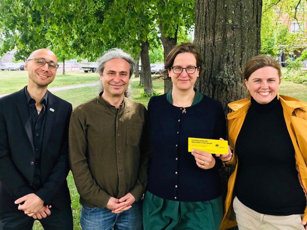Turgut Altug, Silke Gebel und Clara Herrmann stehen vor einem Baum und freuen sich über den Beschluss zur Berliner Baumpflege