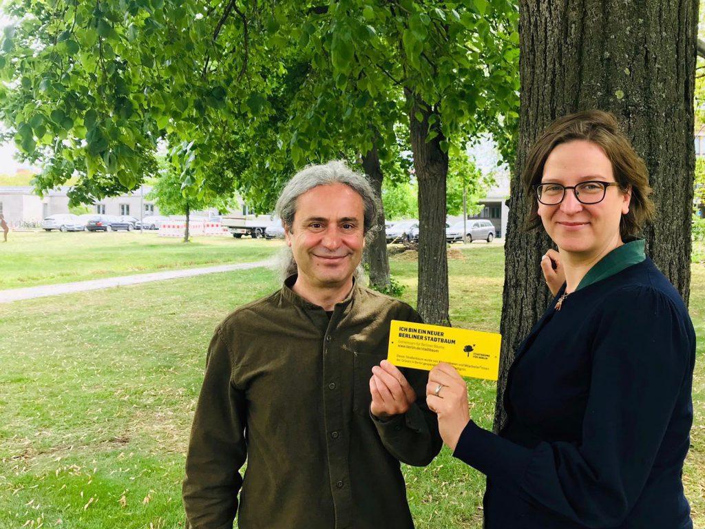 Turgut Altug und Silke Gebel stehen vor einem Baum und freuen sich über den Beschluss zur Berliner Baumpflege