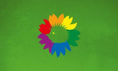 Vor einem grünen Hintergrund ist das Grüne Logo in Regenbogendesign zu sehen