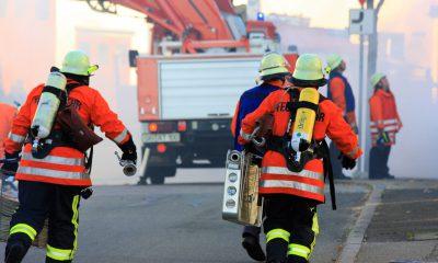 Es sind Feuerwehrleute zu sehen, die wegen eines Einsatzes in voller Montur über die Straße rennen