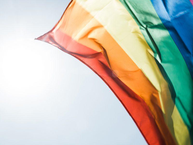 Es ist eine im Sonnenlicht wehende Regenbogenflagge