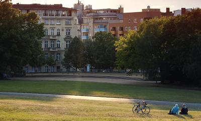 Blick auf eine Häuserreihe am Görlitzer Park bei untergehender Sonne