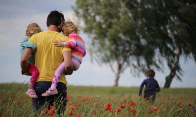 Es ist ein Vater zu sehen, welcher mit seinen drei Kindern über ein Mohnfeld läuft