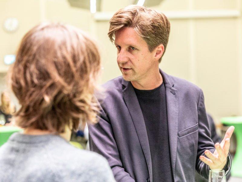 Daniel Wesener unterhält sich beim Grünen Herbstempfang im Berliner Abgeordnetenhaus mit einem Gast