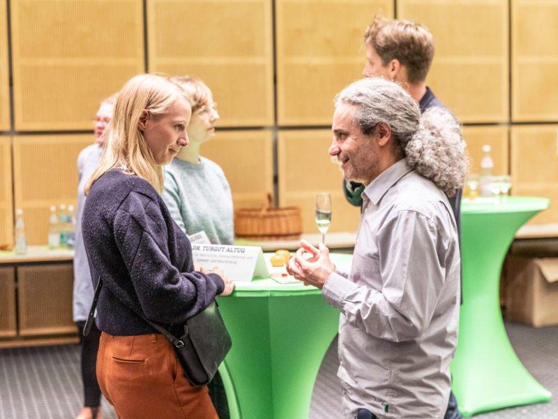 Turgut Altug unterhält sich beim Grünen Herbstempfang im Berliner Abgeordnetenhaus mit einem Gast