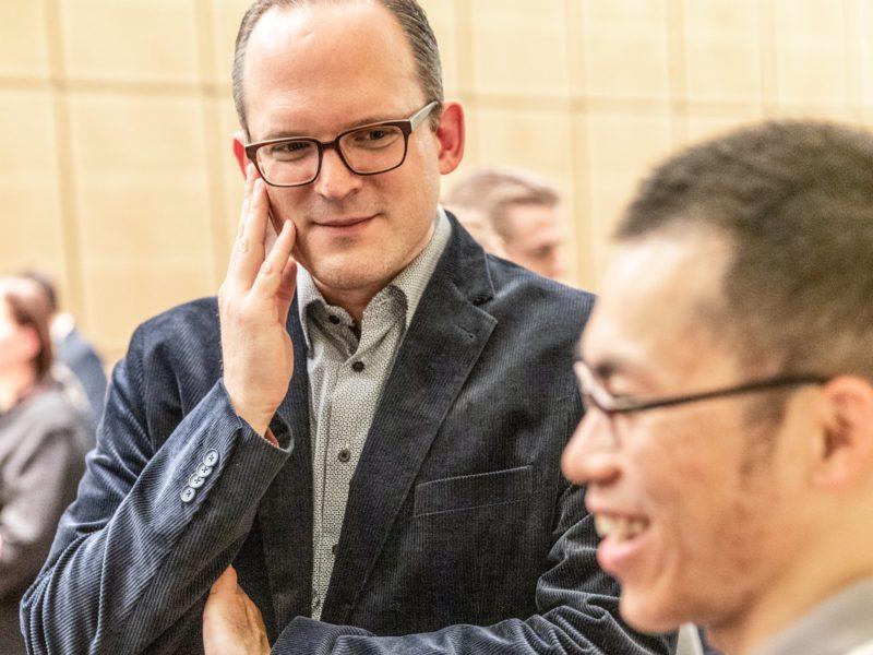 Sebastian Walter unterhält sich beim Grünen Herbstempfang im Berliner Abgeordnetenhaus mit einem Gast