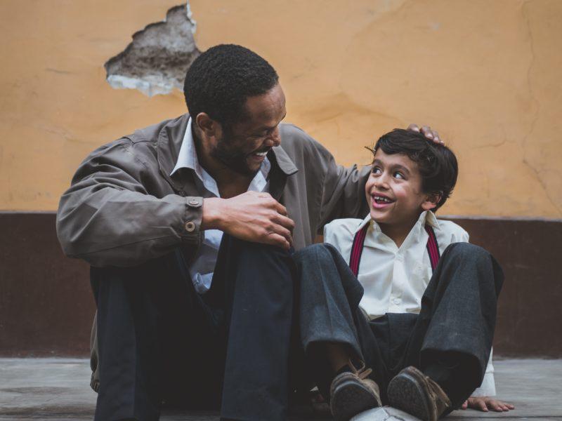 Vater und Sohn unterhalten sich und sitzen auf der Straße mit einem Fußball