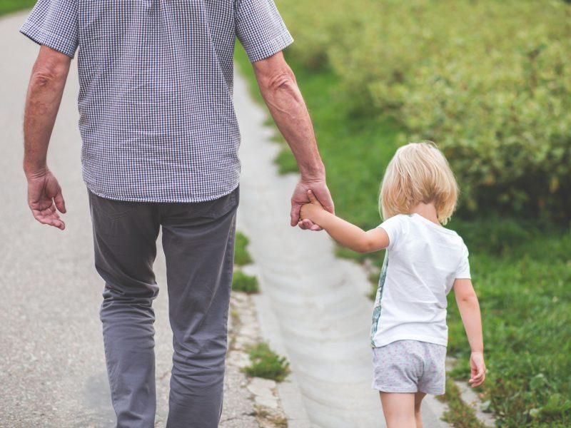 Es ist ein Vater zu sehen, der Hand in Hand mit seinem spaziert