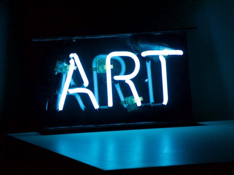 """Es sind Neonschriftzeichen mit dem englischen Wort """"ART"""" zu sehen"""