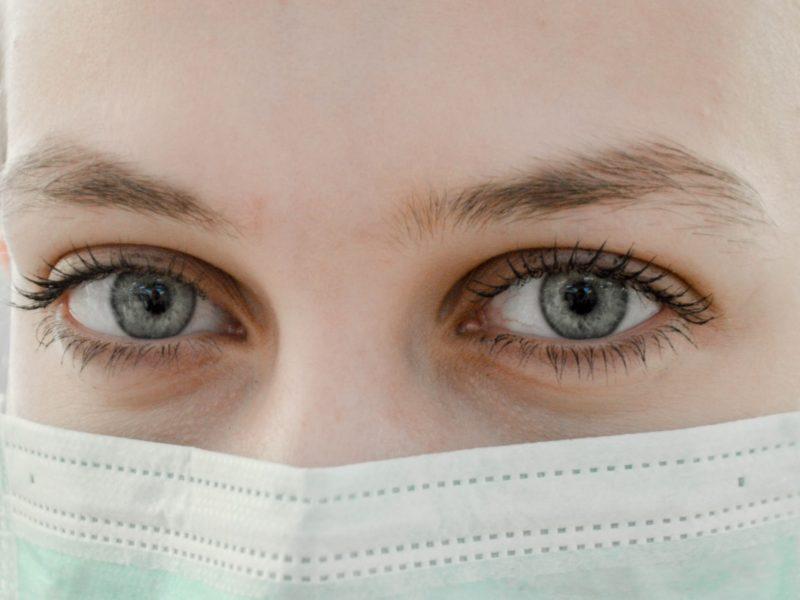 Auf den Foto sieht man eine Krankenschwester mit Mundschutz.