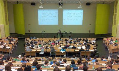 Es sitzen Studierende in einem Hörsaal bei einer Vorlesung