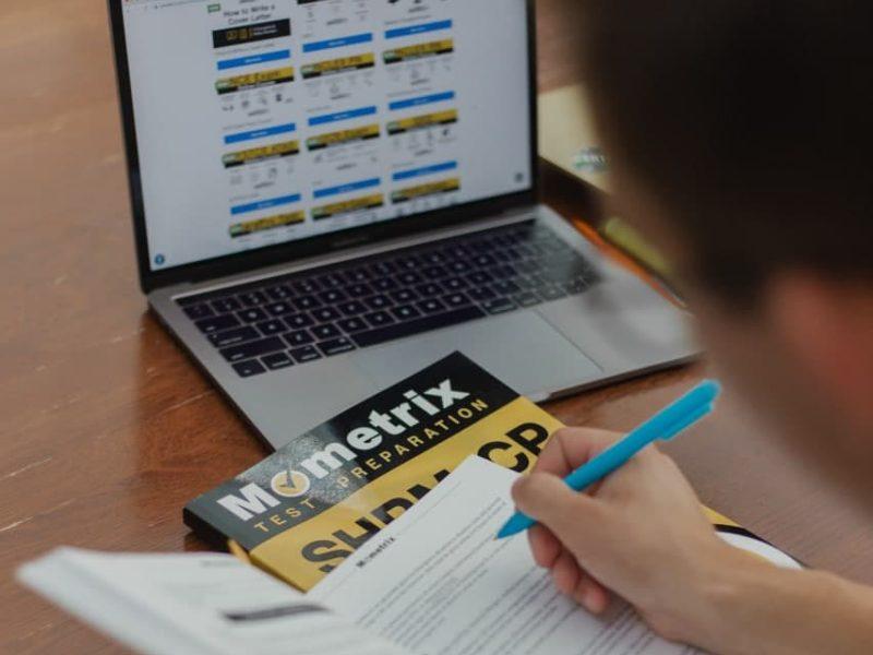 Auf dem Bild ist eine Person mit einem Lehrbuch vor dem Laptop zu sehen.